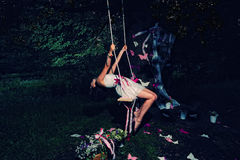 Fairy in the forest. Beautiful fairy girl on the swing in the night forest stock photo