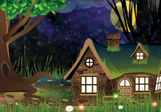 Fairy forest lodge. Lonely house with lighted windows in the scary dark forest Stock Image