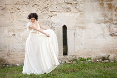 The fairy in the garden. Elegant woman in white long dress looking down while holding the sides of her dress Stock Photo
