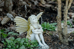 Fairy in the garden. Whimsical fairy with wings sitting in the park Royalty Free Stock Photo