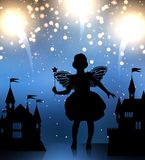 The fairy girl looks at fireworks. The little girl in the costume of the fairy godmother looks up at the fireworks. Next to it are the toy palaces. There is a Royalty Free Stock Photo