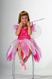 Fairy girl making funny face. Cute toddler girl dressed like a ballerina in a pink dress sitting on a chair making a funny face Royalty Free Stock Photo
