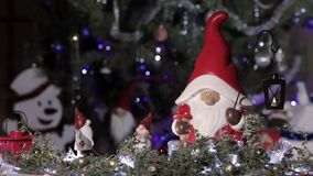 Fairy gnome in a Christmas red cap on a background of a Christmas tree with blinking lights. Christmas and New Year composition.  stock video footage
