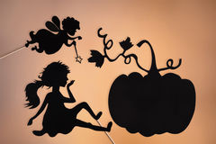 Fairy Godmother, Cinderella and Pumpkin shadow puppets. On the soft glowing screen of shadow theater royalty free stock images