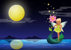 A fairy holding a flower above a boat Royalty Free Stock Photo