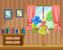 A fairy holding a flower inside the house Royalty Free Stock Image