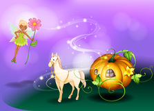 A fairy holding a flower with a pumpkin cart Stock Images