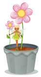 A fairy holding a flower standing on a flower pot Stock Image