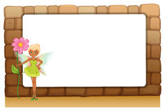 A fairy holding a giant flower beside an empty blankboard on a w Stock Photo