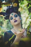Fairy with horns in forest among  trees and branches Royalty Free Stock Image