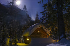 Fairy house, the smoke from the chimney, moonlit winter night. Winter moonlit night, snow and the light from windows of a wooden hut, the smoke from the chimney royalty free stock image