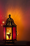 Fairy inside vintage Lantern lit by candlelight with a pattern of stars. Fairy inside lantern illuminated by candle light with brilliant red and gold tones with Royalty Free Stock Photo