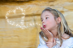 Fairy kisses. Beautiful little girl blowing fairy kisses royalty free stock image