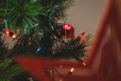 Fairy light and small gift box hanging on christmas tree Royalty Free Stock Photos