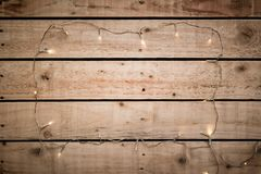 Fairy lights arranged in a frame shape over natural wooden floor or wall background. Empty space for text in centre of illuminated border stock photo