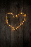 Fairy lights in heart shape. Glowing fairylights on wooden background in the shape of a heart Royalty Free Stock Images