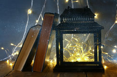 fairy lights inside old lantern and antique books Royalty Free Stock Photo