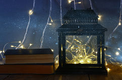 fairy lights inside old lantern and antique books Stock Photography