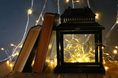 fairy lights inside old lantern and antique books Royalty Free Stock Photography