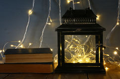 fairy lights inside old lantern and antique books Royalty Free Stock Image