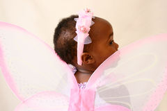 Fairy Looking at something in the distance. Toddler girl in a pink fairy costume with wings and head piece Stock Photography