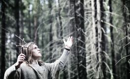 Fairy magician. A sorcerer with a glass sphere, a magical spell. And a ritual. Elder with a staff and a cross in the forest. Black and white magic. A spell in stock photo