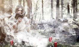 Fairy magician. A sorcerer with a glass sphere, a magical spell. And a ritual. Elder with a staff and a cross in the forest. Black and white magic. A spell in stock photos