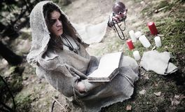 Fairy magician. A sorcerer with a glass sphere, a magical spell. And a ritual. Elder with a staff and a cross in the forest. Black and white magic. A spell in royalty free stock photos