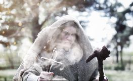 Fairy magician. A sorcerer with a glass sphere, a magical spell. And a ritual. Elder with a staff and a cross in the forest. Black and white magic. A spell in stock images