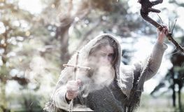 Fairy magician. A sorcerer with a glass sphere, a magical spell. And a ritual. Elder with a staff and a cross in the forest. Black and white magic. A spell in stock image