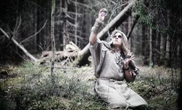 Fairy magician. A sorcerer with a glass sphere, a magical spell. And a ritual. Elder with a staff and a cross in the forest. Black and white magic. A spell in royalty free stock images