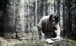 Fairy magician. A sorcerer with a glass sphere, a magical spell. And a ritual. Elder with a staff and a cross in the forest. Black and white magic. A spell in stock photography
