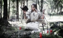 Fairy magician. A sorcerer with a glass sphere, a magical spell. And a ritual. Elder with a staff and a cross in the forest. Black and white magic. A spell in royalty free stock image