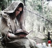 Fairy magician. A sorcerer with a glass sphere, a magical spell. And a ritual. Elder with a staff and a cross in the forest. Black and white magic. A spell in royalty free stock photo
