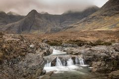 Fairy Pools on the Isle of Skye. Small waterfall under the cloudy sky at the Fairy Pools on the Isle of Skye in Scotland Royalty Free Stock Photo