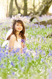 Fairy Princess in Bluebells. Fairy Princess in a sea of Bluebells deep in the woods.  Floral headdress and backlit by sunlight Stock Photography