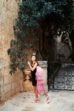 Fairy princess girl in pound and crown walking through the garden of the ancient castle of the city royalty free stock image