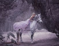 A fairy in a purple, transparent dress with a long flying train lies on a unicorn. Sleeping Beauty. Blonde girl walking