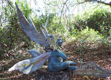 Fairy sculpture sitting on a log in the garden Royalty Free Stock Image