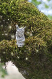 Fairy sitting on mossy branch with sparkles of light glowing around her. Royalty Free Stock Photos