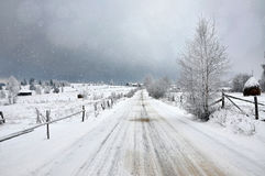 Fairy snowy winter landscape with a snow covered rural road Stock Photos