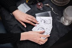The fairy spreads the tarot cards, the magical meaning of the symbols. Fortune-telling from tarot cards. Fairy predicts the future by arranging tarot cards royalty free stock image