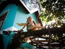 Fairy with dragonfly wings sitting at a wooden pergola stock photo