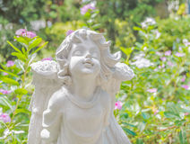 Fairy Statue in the garden with flower Stock Photo