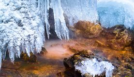 Fairy stream with colored stones and hanging icicles, Rainbow Falls, Russia royalty free stock photo