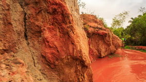Fairy-Stream Rocks Distant Tourist Walks along Red Waters. View of Fairy-Stream pitted rocks distant tourist with backpack walks barefoot along shallow red stock video footage