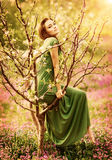 Fairy-tail forest nymph. Beautiful woman at spring garden, wearing long dress, sitting on blooming tree, vintage dreamy fashion style stock photo