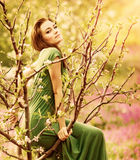 Fairy-tail forest nymph. Beautiful woman at spring garden, wearing long dress, sitting on blooming tree, vintage dreamy fashion style royalty free stock photography