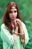 Red-haired upset, unhappy girl with blue eyes with connected hands Royalty Free Stock Photos