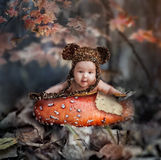 Fairy tale in autumn forest. Cute baby laying in mushroom in dark october forest royalty free stock photo